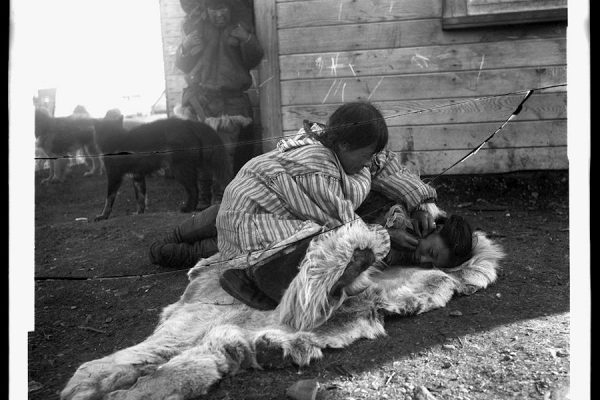 Lantern slide of a Siberian Yupik woman skin-stitching at Indian Point (Ungaziq), Chukotka, 1901. Photographer Waldemar Bogoras.